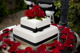 A white wedding cake with red rose decorations. [url=search/lightbox/4540529] [img]http://richlegg.com/istock/banners/wedding_banner.jpg[/img][/url] [b][url=search/lightbox/4540529]Click HERE to see my other WEDDING images[/url][/b]